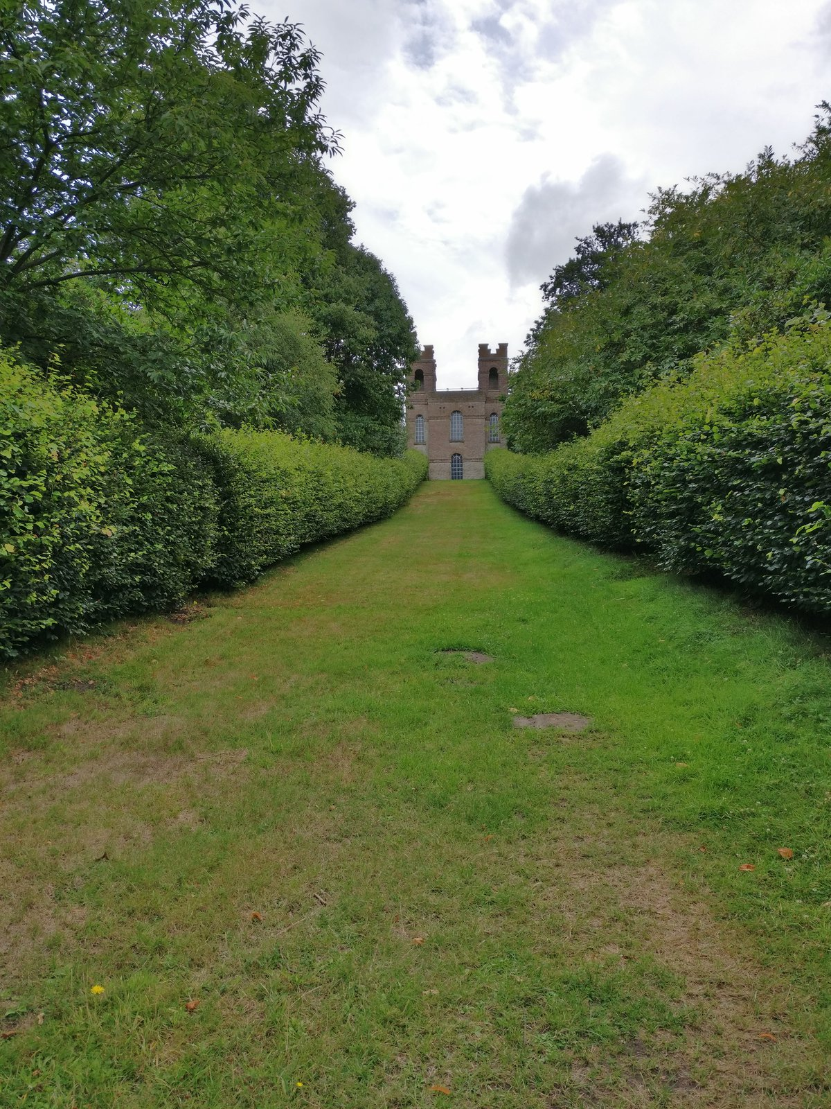 Building after hedge lined path
